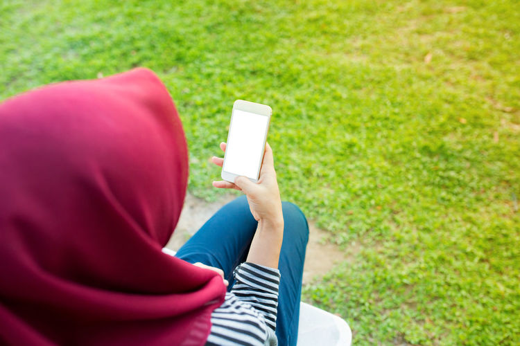 High Angle View Of Woman Wearing Hijab Using Mobile Phone While Sitting In Park