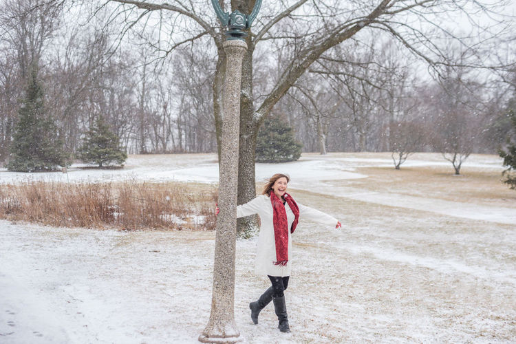 Smiling woman walking on snowy field during snowfall