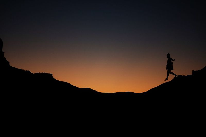 Silhouette girl walking on mountain against clear sky