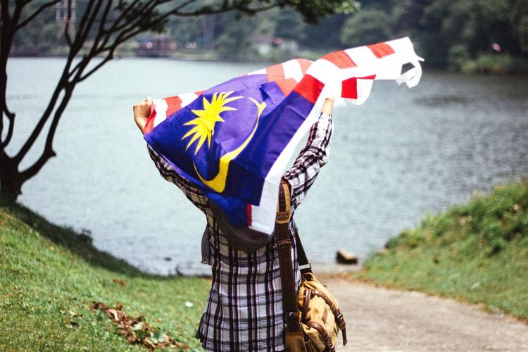 Young woman holding a waving Malaysian flag. Malaysia Asian  EyeEm Vision Flag People Young Woman Girl Waving Merdeka Patriotic