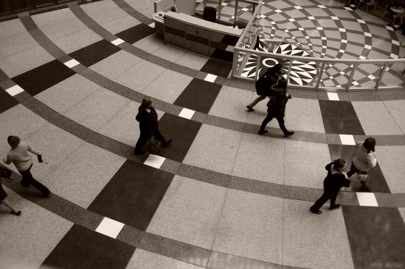 High angle view of people walking on patterned flooring