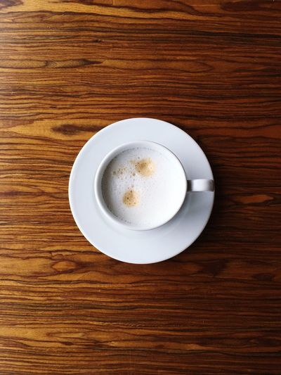 Cappuccino on a wooden table Table Refreshment Drink Directly Above Food And Drink Coffee Cup Coffee - Drink Frothy Drink Saucer Wood - Material Freshness No People Indoors  Cappuccino Close-up Froth Art Day