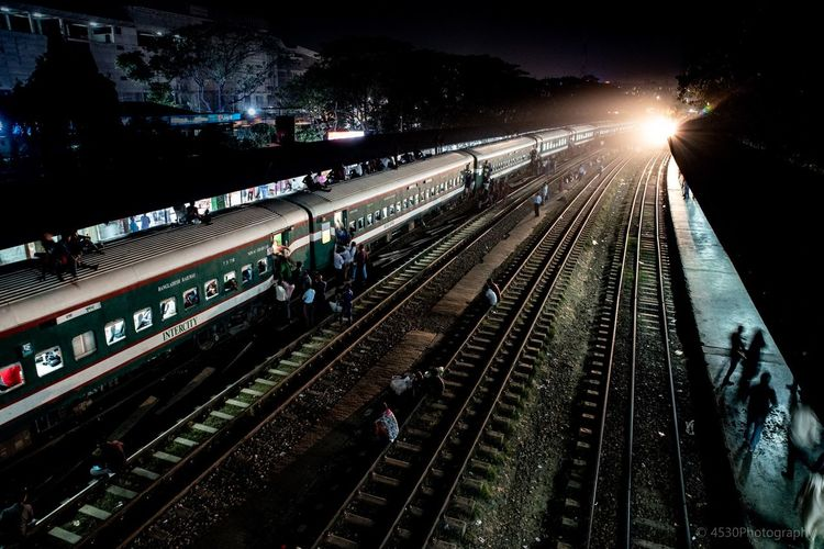 High angle view of people and train on railroad tracks at night