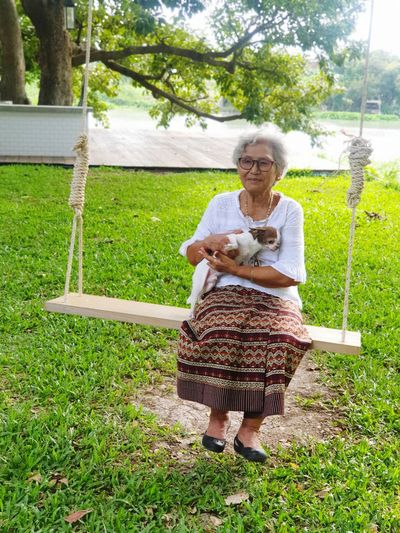 Full length of woman standing on grass in yard