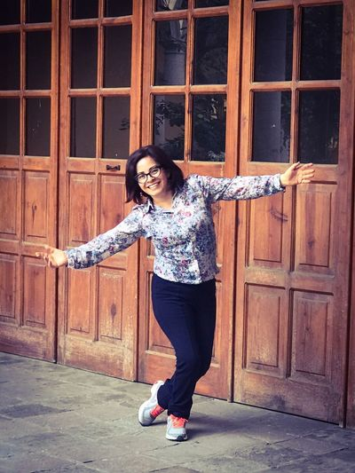 Portrait Of Happy Young Woman With Arms Outstretched By Wooden Doors