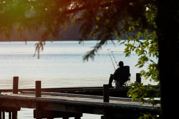Fishing at the lake on the dock Relaxing Beauty In Nature Day Fishing Lake Leisure Activity Lifestyles Nature One Person Outdoors Silhouette Tree Water