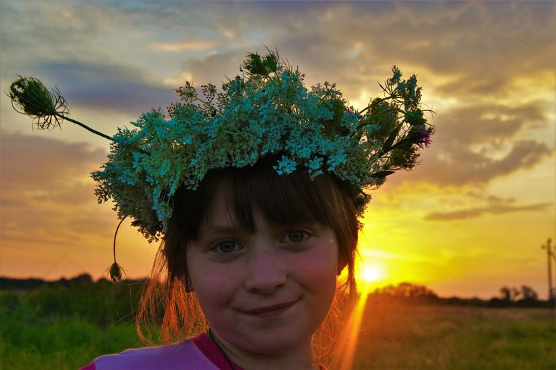 Portrait of smiling girl wearing flowers against cloudy sky during sunset