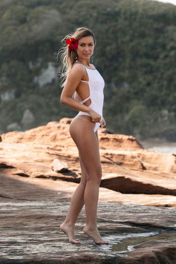 Seductive young woman wearing white swimsuit while standing on rock at beach