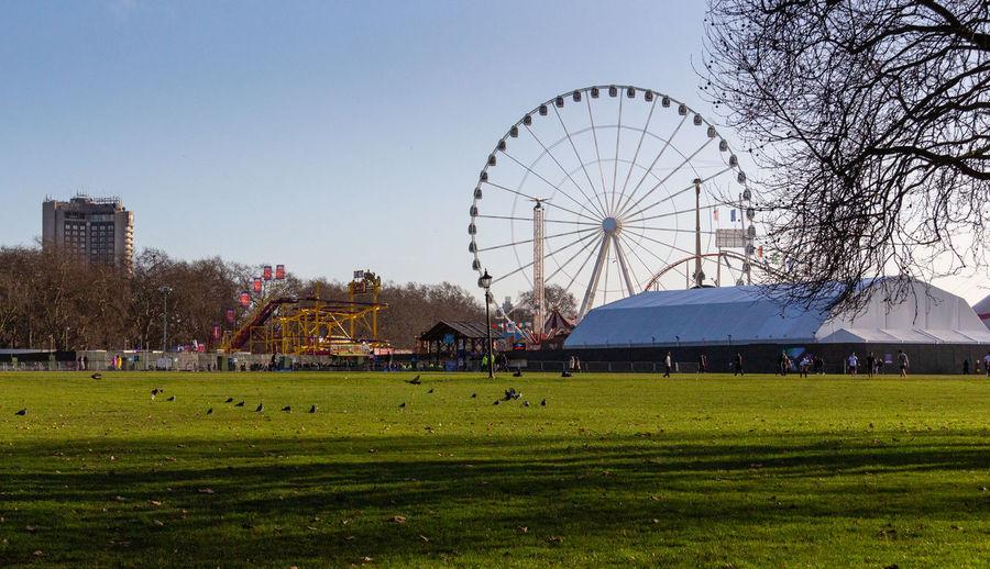 Ferris wheel on field against clear sky