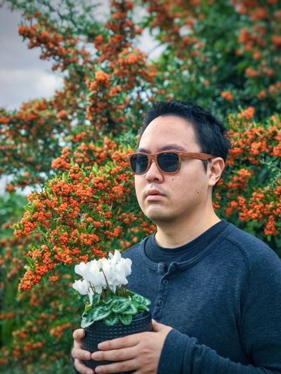 Portrait of young man holding white flowering cyclamen potted plant against yellow berry rowan tree.