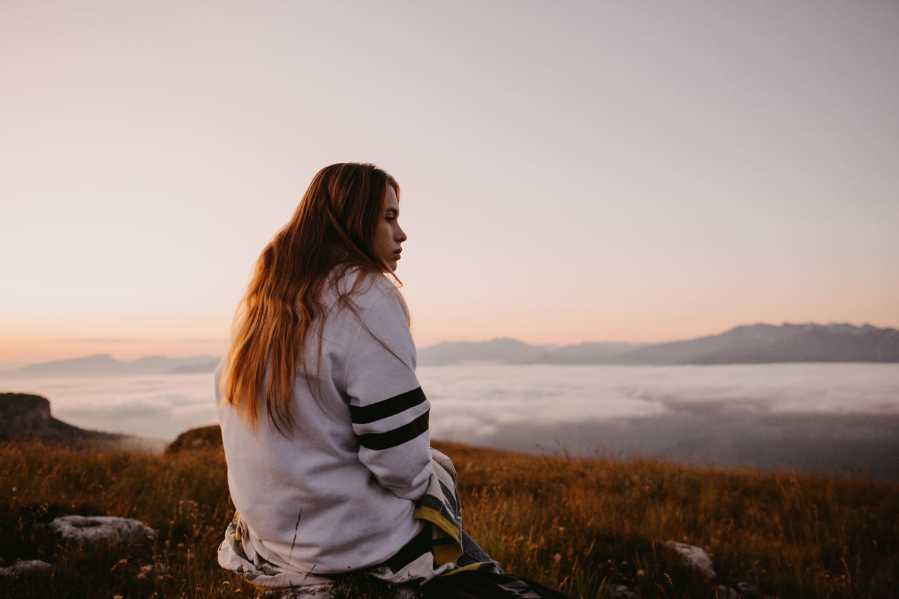 Woman looking away while sitting against sky during sunset