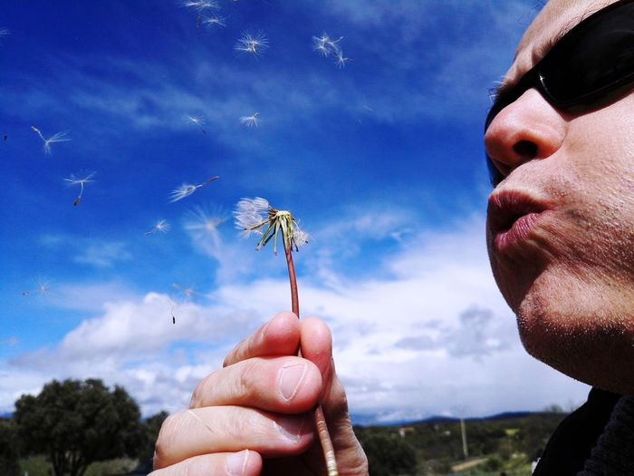 Close-Up Of Man Blowing Dandelion Seeds Against Sky