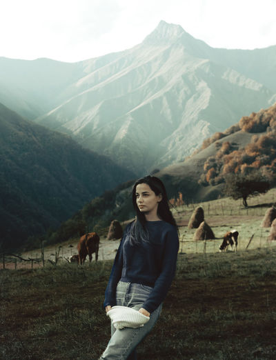 Young woman looking away while standing on grass against cows and mountains