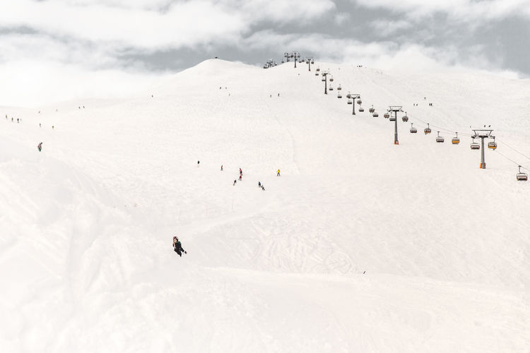 People Skiing By Ski Lift On Snowcapped Mountains During Sunny Day