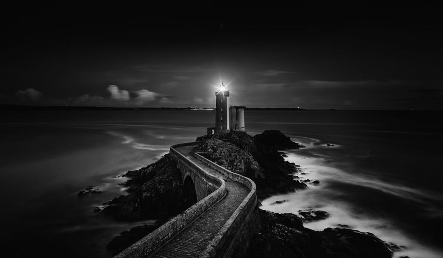 Illuminated Lighthouse At Beach During Night