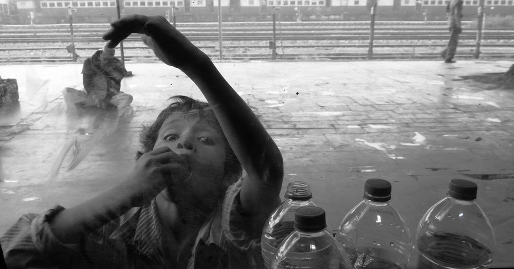 Portrait Of Homeless Boy Looking Through Glass Window At Railroad Station