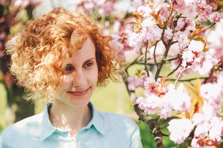 Blonde Branch Casual Clothing Cherry Blossoms Cherry Tree Close-up Curly Hair Natural Light Portrait Flower Focus On Foreground Fragility Girl Headshot Leisure Activity Lifestyles Long Hair Nature Outdoors Park Person Pink Color Portrait Shirt Smile Spring Springtime Decadence