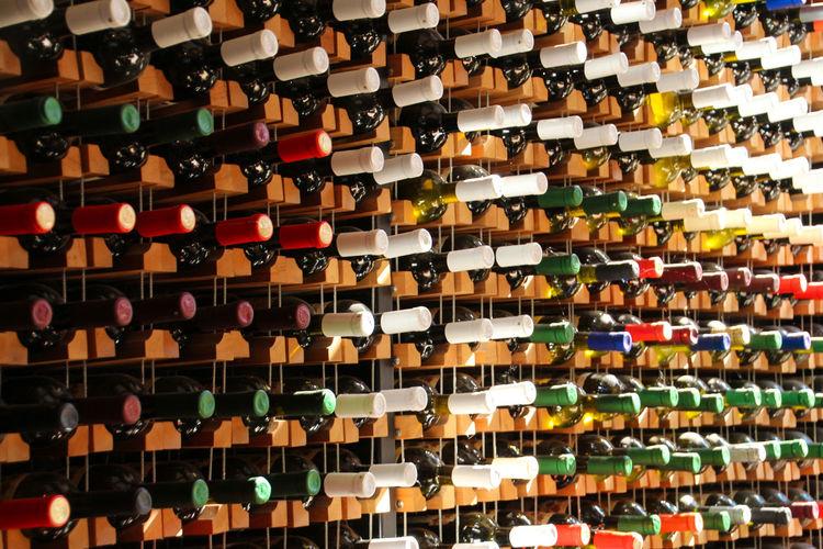 Full frame shot of multi colored wine bottles in rack