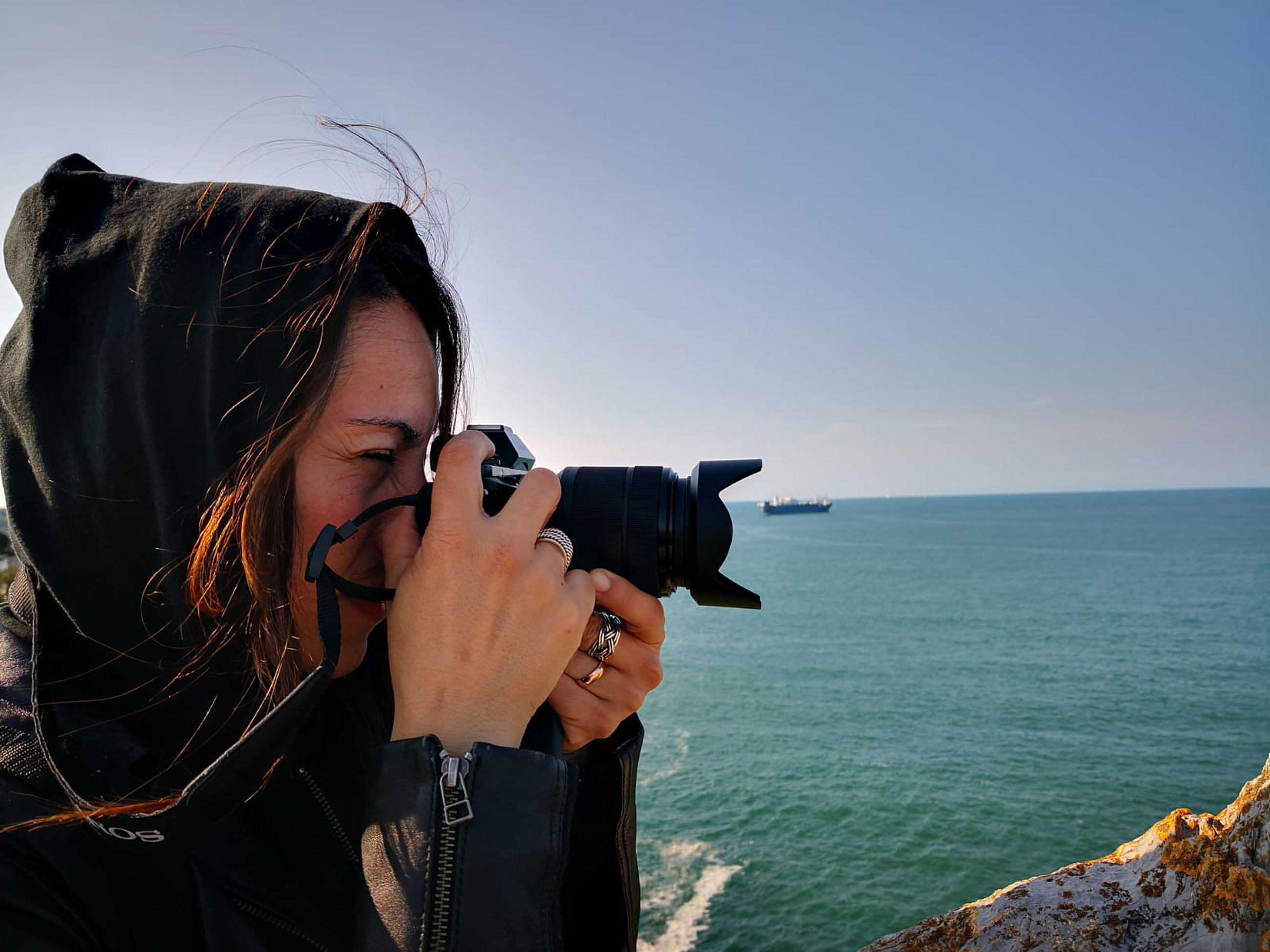 sea, sky, one person, leisure activity, technology, young adult, water, horizon over water, horizon, real people, lifestyles, photography themes, activity, holding, young women, camera - photographic equipment, photographing, standing, hair, hairstyle, wireless technology, outdoors, digital camera