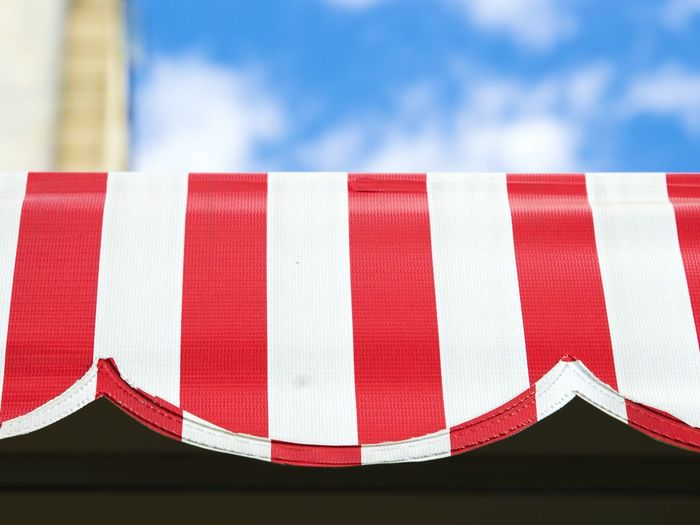 Low angle view of striped awning against sky