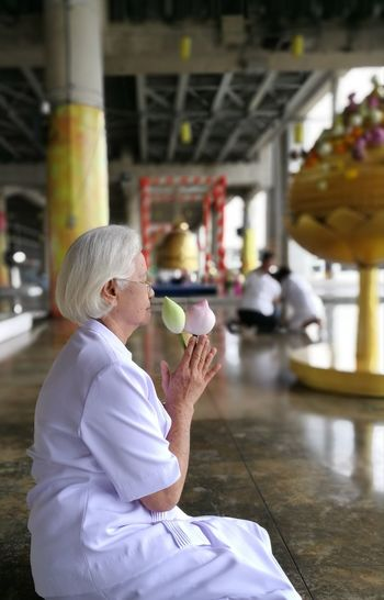 Woman holding flower buds in temple