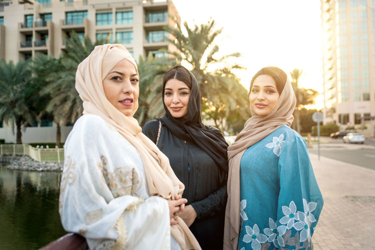 Portrait of young women in hijab standing on footpath