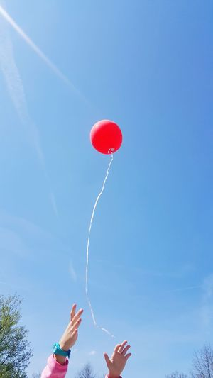 Low Angle View Of Girl Reaching Balloon Flying Against Blue Sky