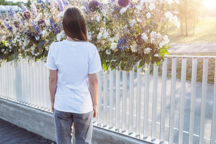 Portrait of young women who wears white t-shirt and posing against a background, back view.