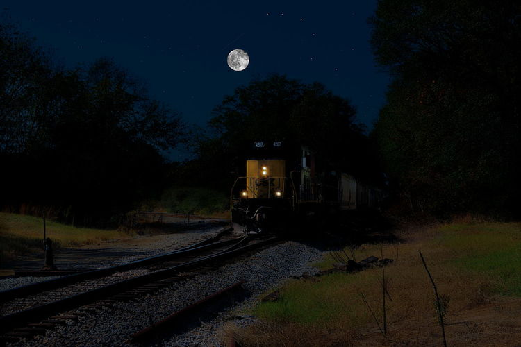 Train on railroad track against sky at night