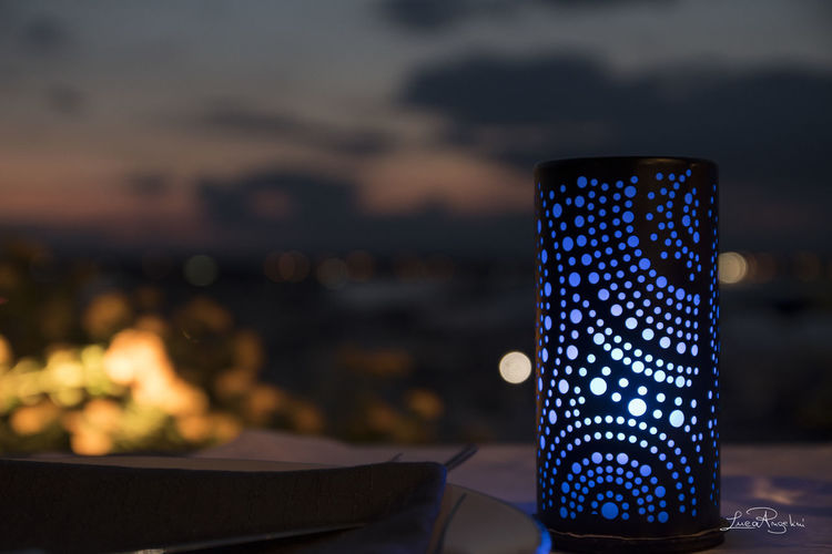 Close-up of illuminated lighting equipment on table against sky at sunset