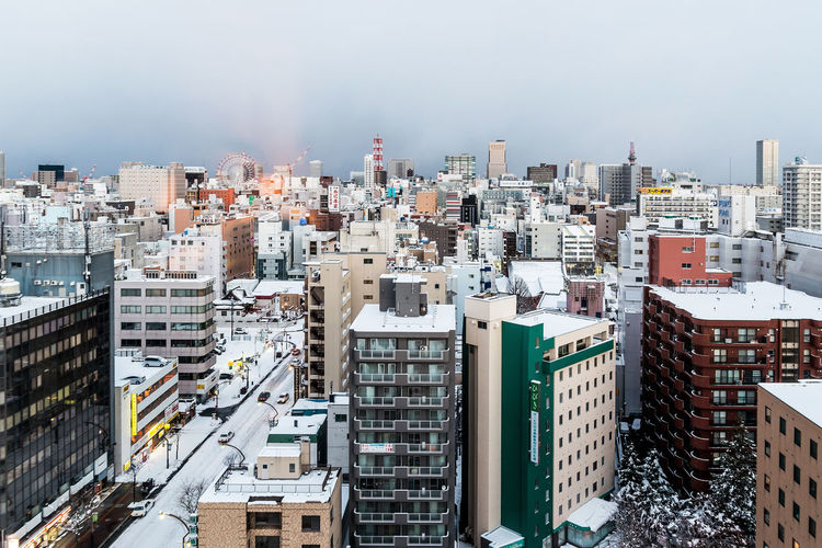 High angle view of city buildings during winter season against cloudy sky