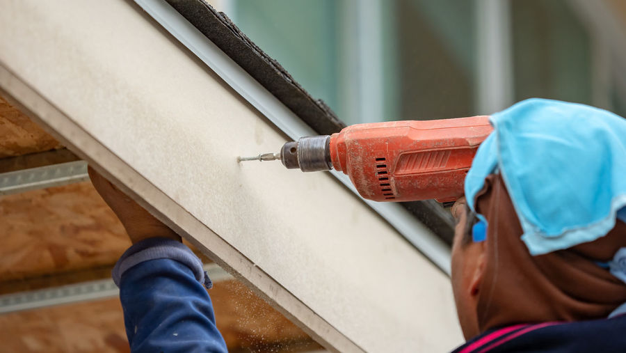 Close-Up Of Manual Worker Drilling Roof At Construction Site