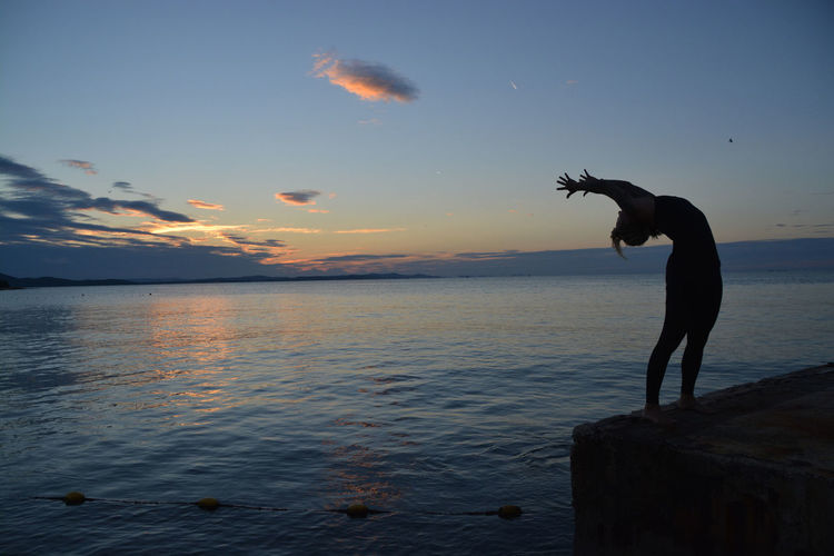 Woman doing yoga at the coastline Beauty In Nature Cloud - Sky Evening Horizon Over Water Idyllic Leisure Activity Nature Real People Scenics Sea Sea And Sky Silhouette Sky Space For Text Sport Sports Summer Sunset Tranquil Scene Tranquility Water Woman Yoga Yoga Pose First Eyeem Photo