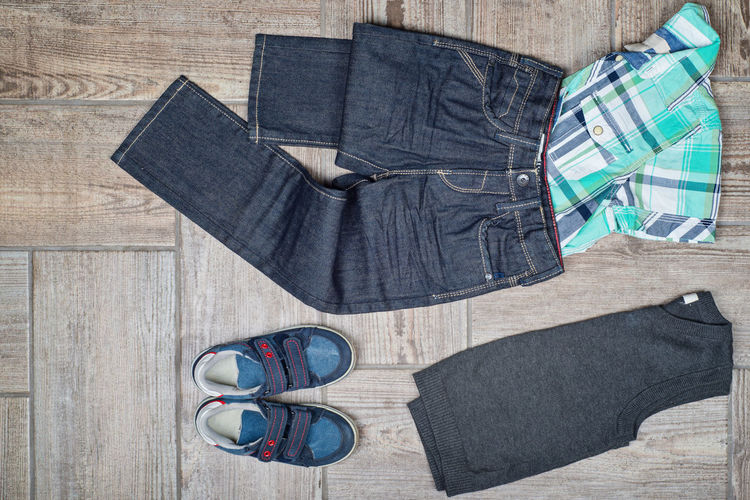 Flat lay of clothes and shoes on wooden floor