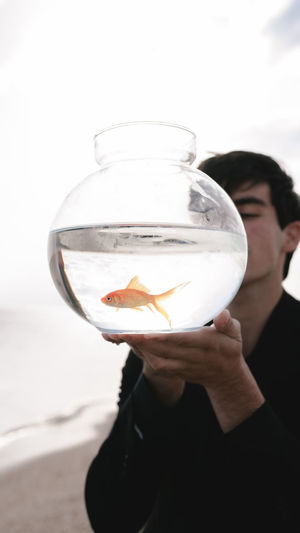 Man holding fish in glass