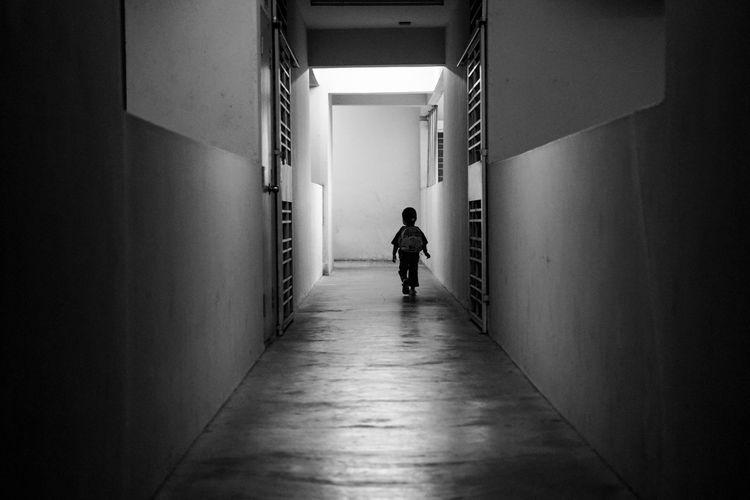 Rear View Of Boy Walking In Corridor