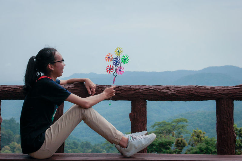 Side view of young woman sitting with pinwheel toy against sky
