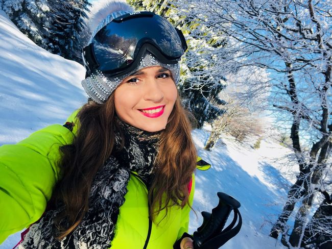 Portrait of smiling young woman wearing Uvex ski glasses with trees covered in snow in the background Trees Forest Young Pretty Sunny Ski Glasses Skier Selfie Face Cold Temperature Snow Winter Looking At Camera Portrait Smiling Mountain Only Women Warm Clothing One Person Jacket Happiness One Woman Only Front View Skiing Adult People Headwear Sport