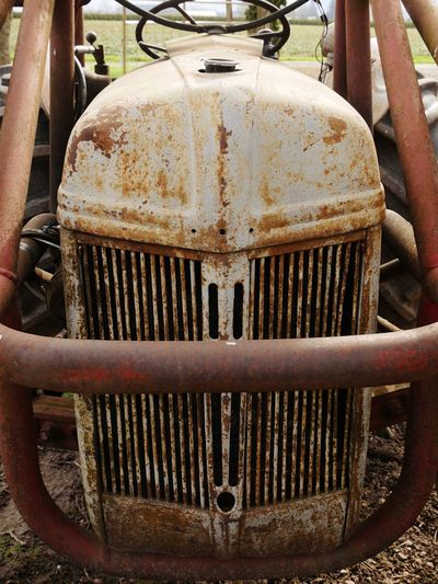 Old farm tractor grill. Rust Tractor Farm Equipment Metal Close-up Rusty Day Abandoned Old Decline Run-down Focus On Foreground Equipment