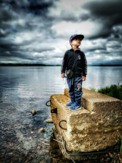 Boy standing on rock by sea against sky