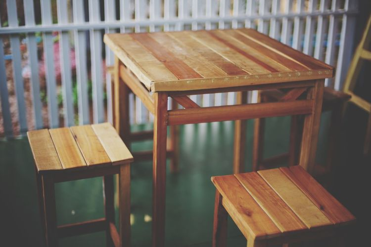 Empty wooden table chair set on porch