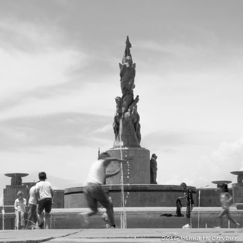 Statue in front of monument against sky