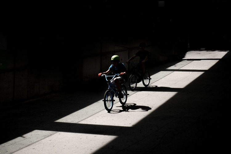 Boys riding bicycle in city