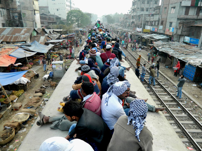 People sitting on train rood in city