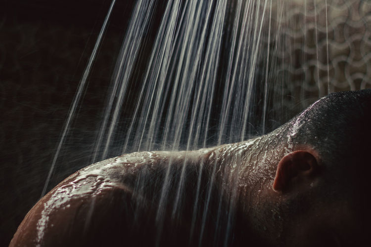 Close-up of man taking shower