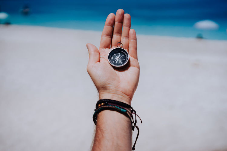 Low section of person holding ring at beach against sky