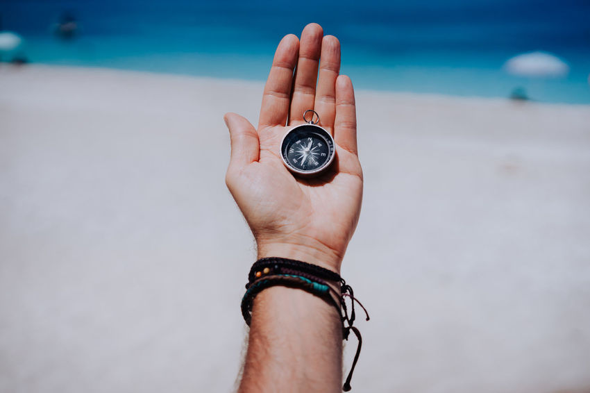 One open stretched hand palm with black metal compass on the sandy beach. Find your wish goal way concept. Blue sea in background. Point of view pov. Beach Body Part Clock Compass Finger Hand Holding Horizon Over Water Human Body Part Human Finger Human Hand Land Nature One Person Outdoors Personal Accessory Pocket Watch Point Of View Real People Sea Sky Time Watch Water Wristwatch