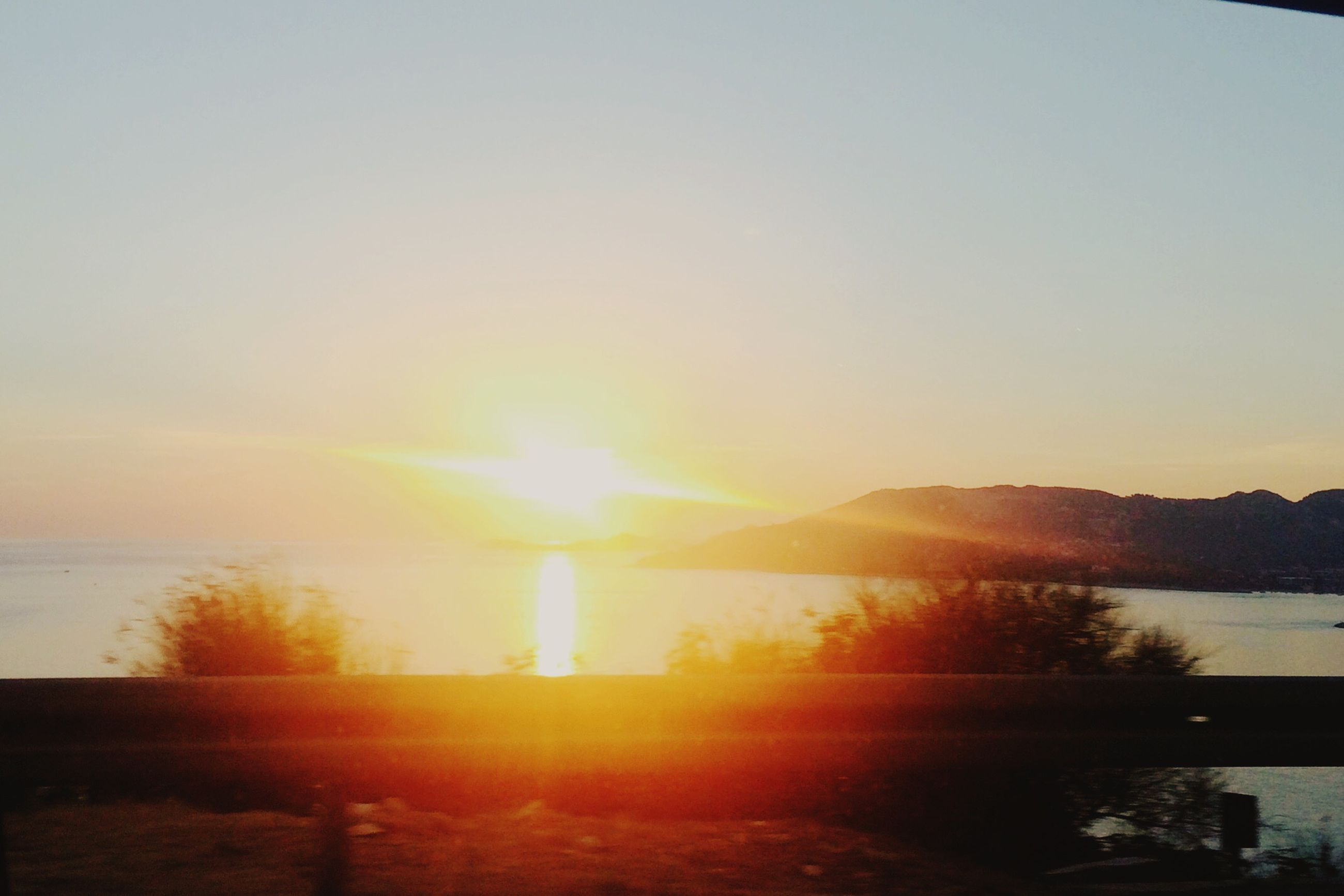 sunset, tranquil scene, scenics, sun, water, tranquility, beauty in nature, sunbeam, sunlight, mountain, reflection, lake, orange color, idyllic, majestic, lens flare, non-urban scene, nature, glowing, bright, sky, sea, calm, outdoors, standing water, remote, vibrant color, mountain range, romantic sky, no people