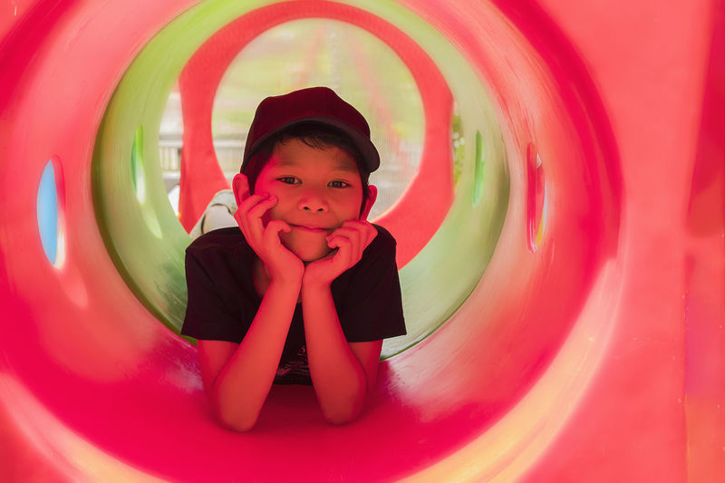 Portrait of smiling boy lying on tube slide in playground