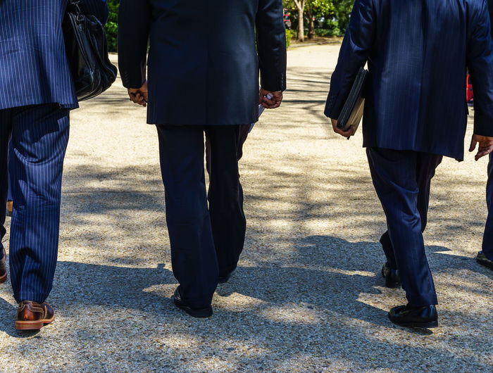 Low Section View Of Three Businessmen Walking